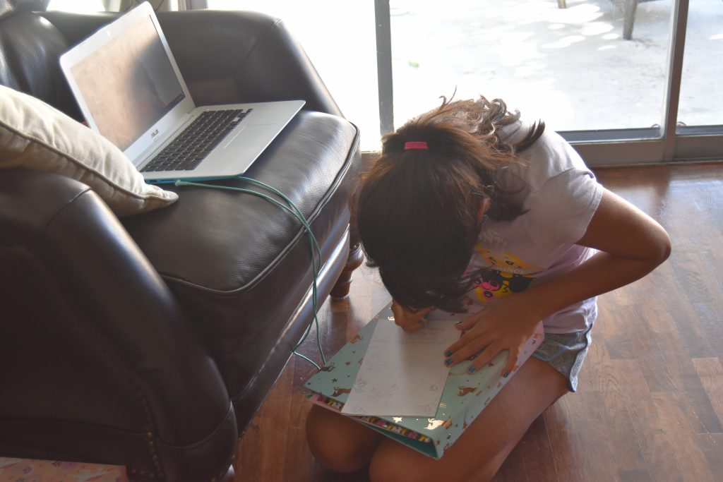 Homework help- kid working and sitting on the floor
