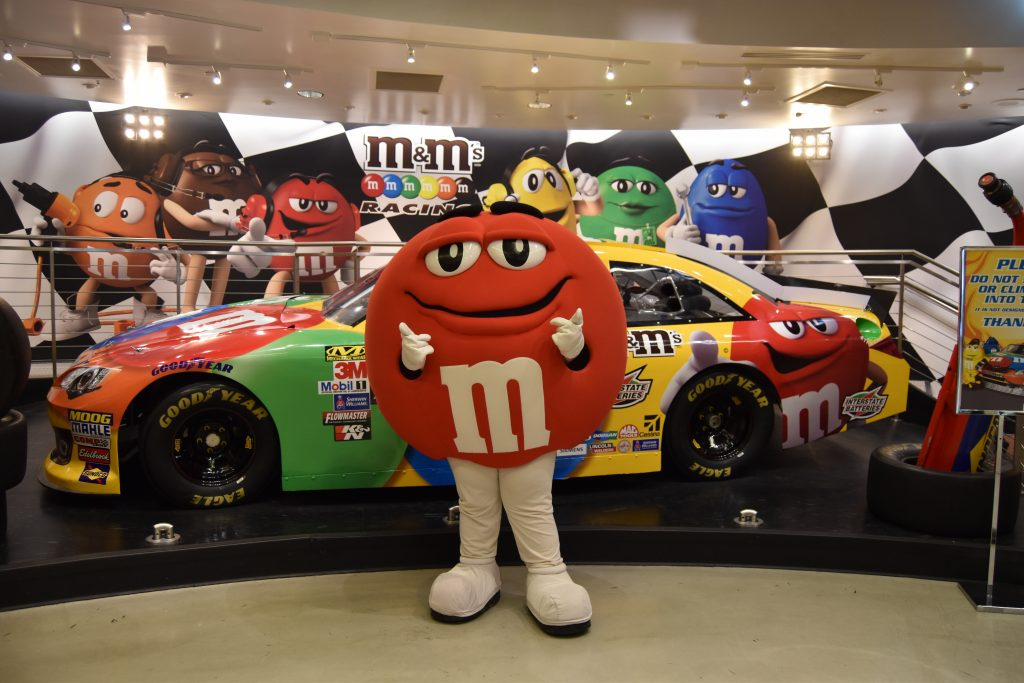 M&M standing in front of NASCAR race car