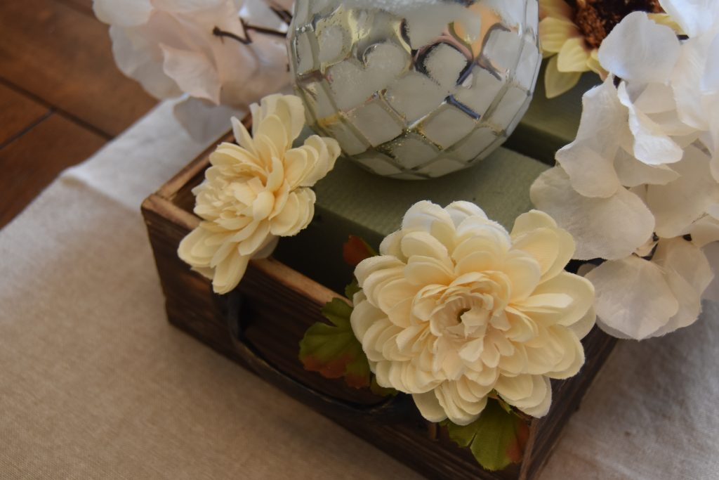 Easy DIY Fall Centerpiece-Two cream color flowers placed at end of wooden box, pointing outward.