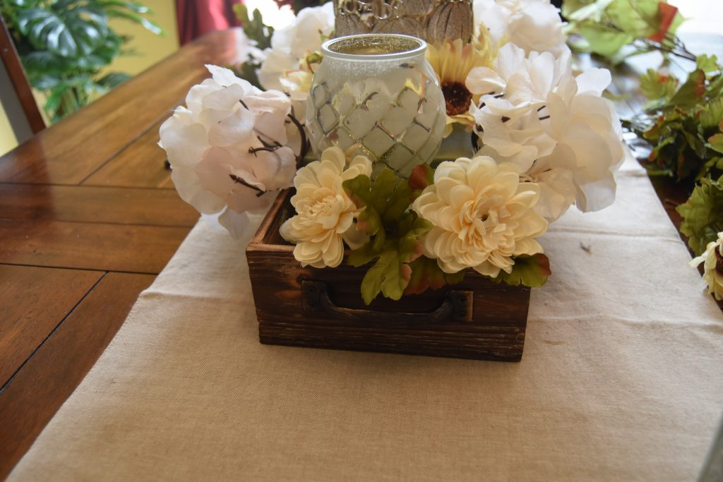 Easy DIY Fall Centerpiece-Green leaves placed between cream color flowers.