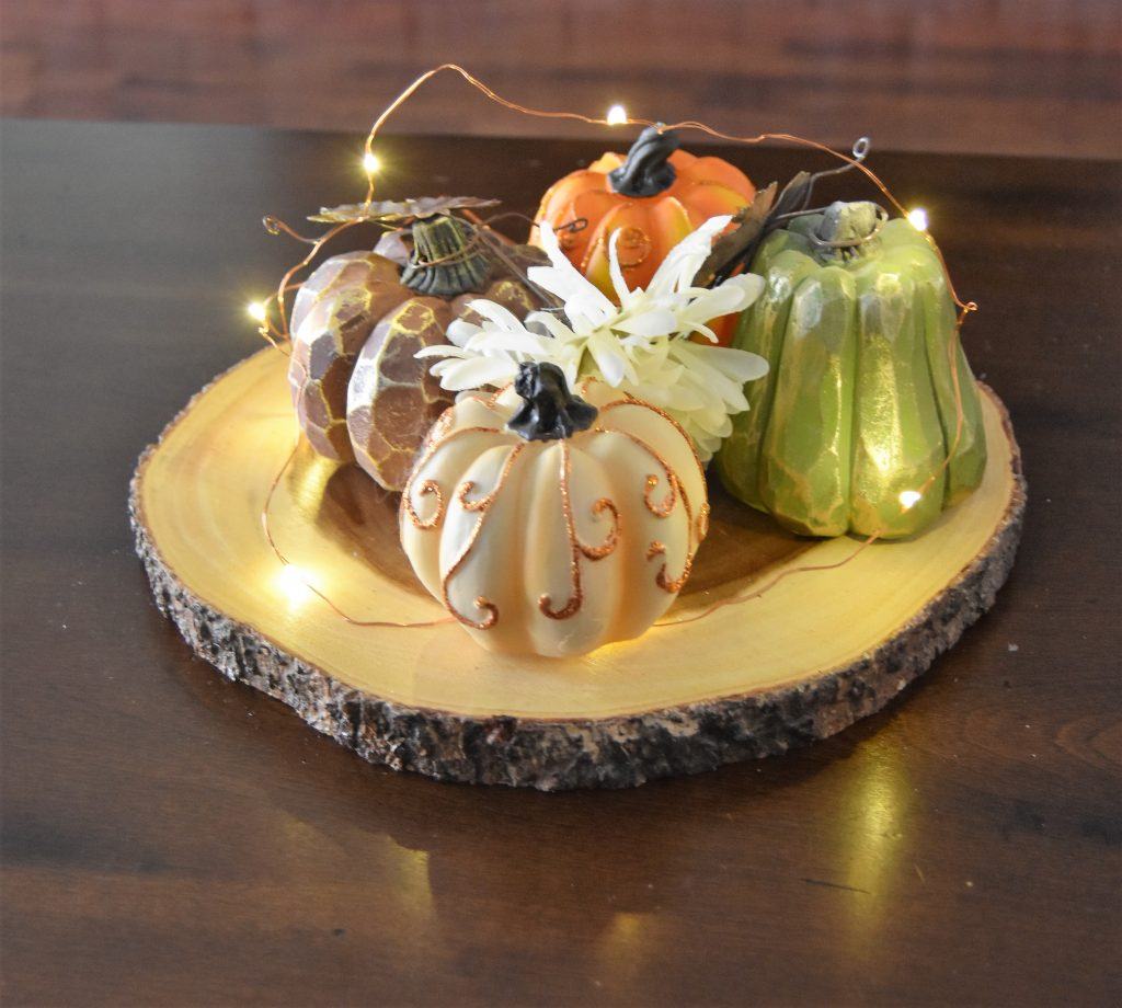 Simple Fall Home Decor-Wood slab with decorative mini-pumpkins, twinkle lights, and leftover faux flowers