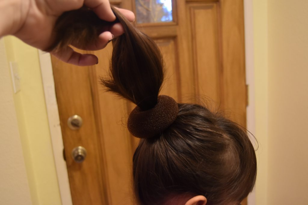Fall-Inspired Crazy Hair Day Style-Pulling pony tail through foam donut bun
