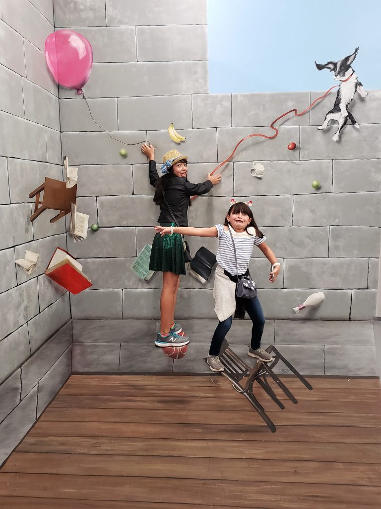 Girls balancing on objects- Hollywood Museum of Illusions