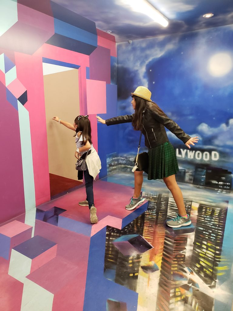 Girls crossing skyscraper buildings- Hollywood Museum of Illusions