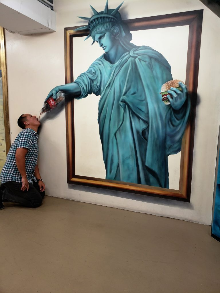 Man drinking soda from Statue of Liberty- Hollywood Museum of Illusions