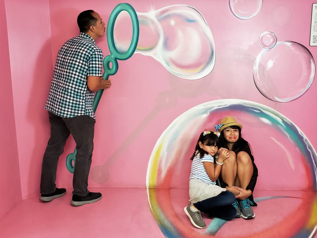 Man blowing bubble with kids trapped inside- Hollywood Museum of Illusions