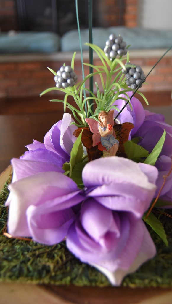 Fairy seated on chair in center of floral circle-Fairy Cloche Centerpiece DIY