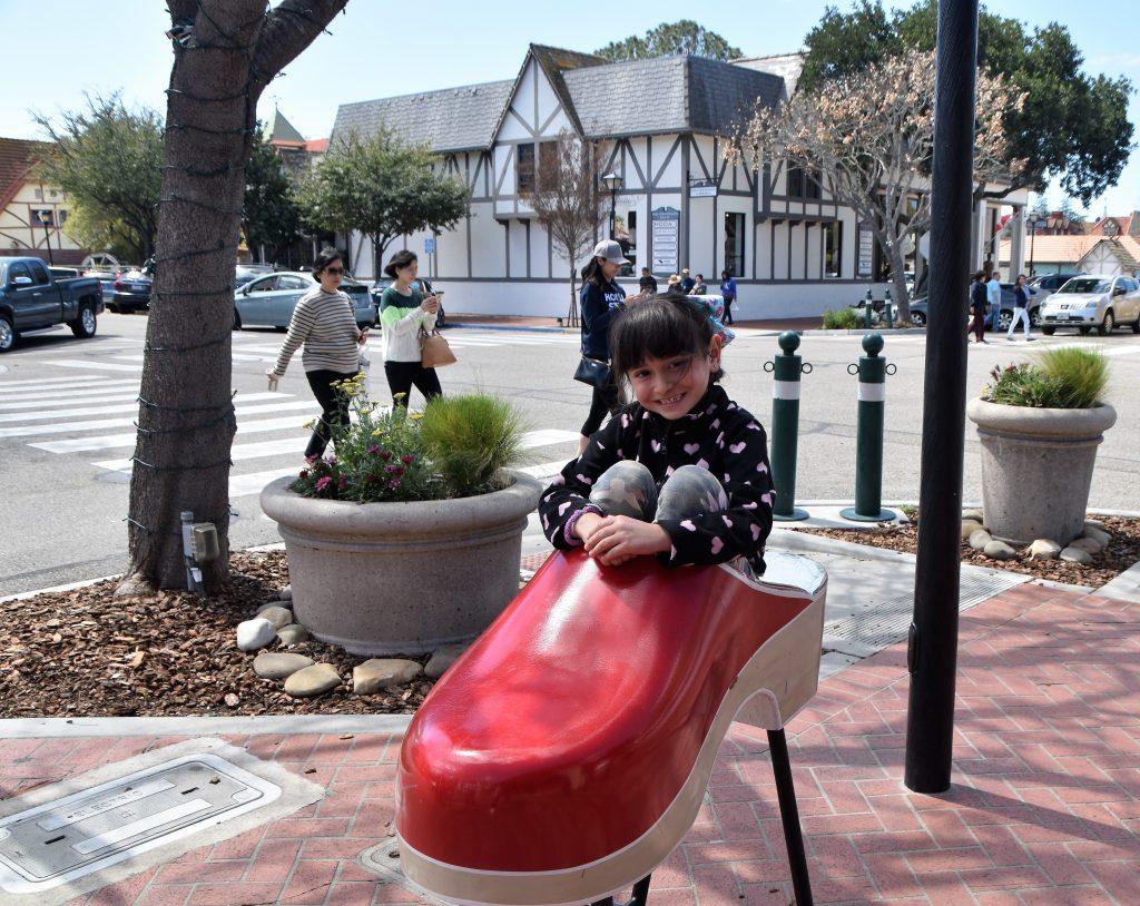 Girl sitting inside a wooden shoe-Instagram Worthy Photo Opps In Solvang