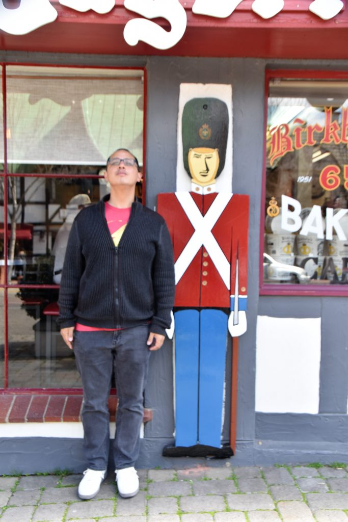 Man posing next to wooden soldier-Instagram Worthy Photo Opps In Solvangage: Is It Worth It?